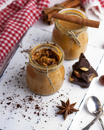 Caramel dessert Toffee in a glass jar on a white wooden board, top view Stock Photo