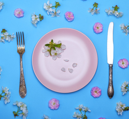 empty round pink ceramic plate and a vintage knife with a fork on a blue surface in the middle of pink and white buds of cherry, top view