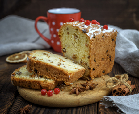 baked big cake with dried fruit and cut into slices on a wooden board, brown table