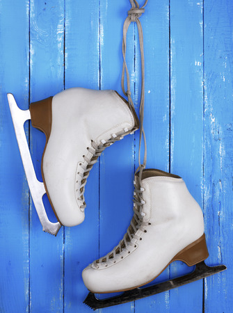 pair of white leather female skates for figure skating hanging on a blue wooden background Stock Photo