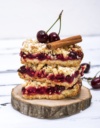 pile of baked cake with cherry, close up