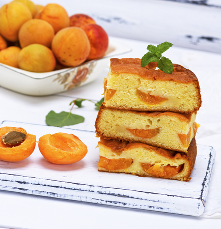 stack of biscuit pie with apricots on a white wooden table, sponge cake Archivio Fotografico
