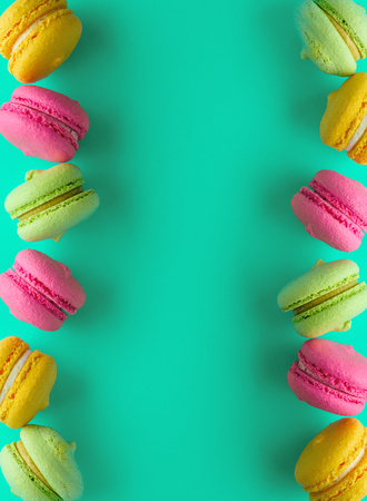 multicolored cakes of almond flour with cream macarons, copy space in the middle, top view
