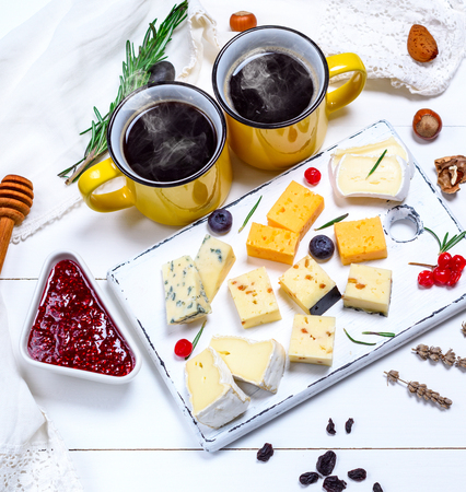 two yellow cups of coffee and small pieces of brie cheese, roquefort, camembert, cheddar and cheese with walnuts on a white wooden board, top view 写真素材