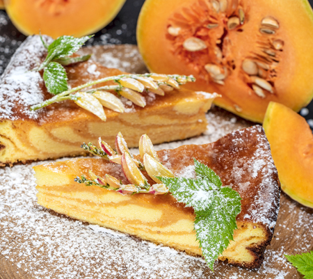 pieces of pie with fresh pumpkin sprinkled with powdered sugar on a brown board
