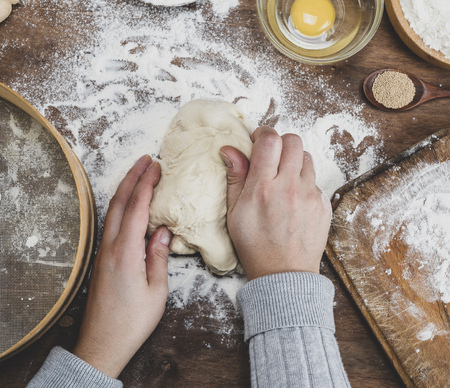 hand kneaded dough on brown wooden table, top view