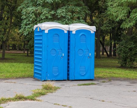 Two blue booths of the biotoilete stand in the middle of the city park on a summer day Stock Photo