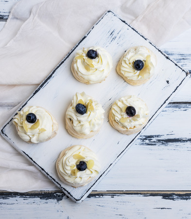 small baked round cake meringue with whipped cream on a white wooden board, top view