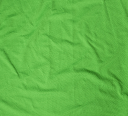 green crumpled stretching soft fabric, full frame, close up