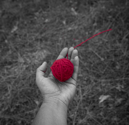 red wool clew in human hand, top view, close up
