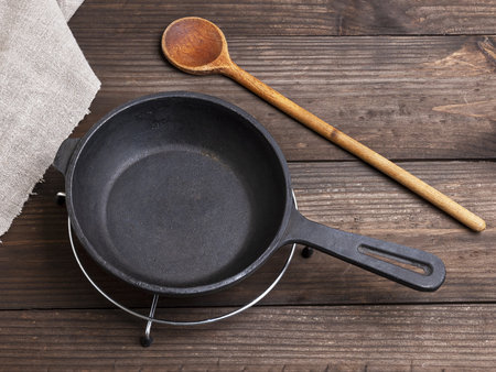 empty black round cast iron pan, spoon on a brown wooden table, top view 免版税图像