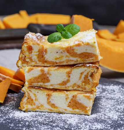 stack of square pieces of baked cheesecake cottage cheese with pumpkin sprinkle with powdered sugar Stockfoto