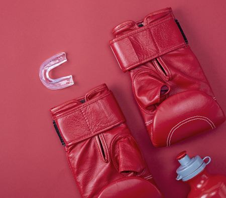 red boxing sport gloves, silicone mouthpiece for the teeth on a red background, top view Stock Photo