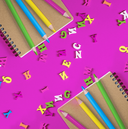 two notebook and multicolored wooden pencils on a pink background, the letters of the English alphabet are scattered