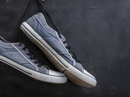 pair of textile blue sneakers hang on a string on a black background, copy space Stock fotó