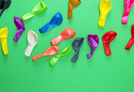 colorful deflated balloons on a green background, copy space