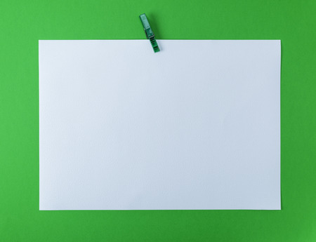 white blank drawing sheet on green plastic clothespin, green background, copy space Archivio Fotografico