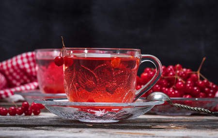 hot viburnum tea in a transparent cup with a handle and saucer on a gray wooden table, next to fresh berries Stock Photo