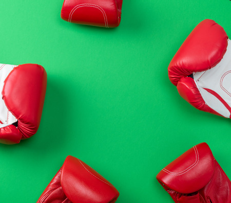 abstract green background with red leather boxing gloves, empty space in the middle Stock Photo