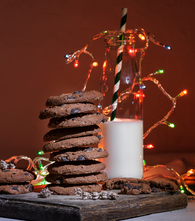 stack of chocolate round biscuits, a glass bottle with milk and a bright Christmas garland, festive background 스톡 콘텐츠