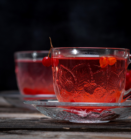 viburnum tea in a transparent cup with a handle and saucer, close up