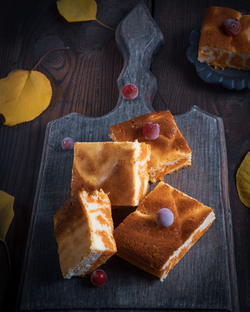 baked square pieces of pumpkin cheesecake on a wooden board, top view Stockfoto