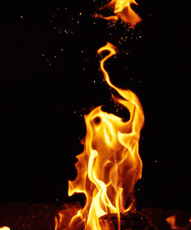 bright orange and yellow flames with sparks, close up