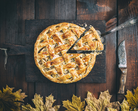 classic American apple pie with puff pastry on an old brown kitchen board and iron spatula, top view