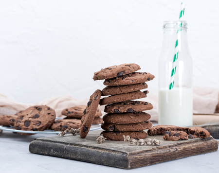 stack of round chocolate chip cookies and a glass bottle with milk on a brown wooden board