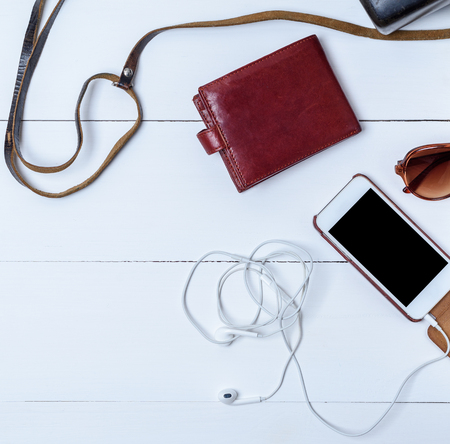 white smartphone with a blank black screen, brown leather wallet on a white wooden background