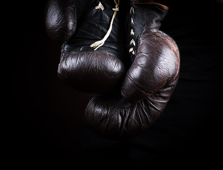 pair of very old brown boxing gloves hanging, black background Stok Fotoğraf
