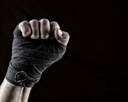 lifted up fist of athlete wrapped in black textile bandage, gesture of solidarity Banco de Imagens