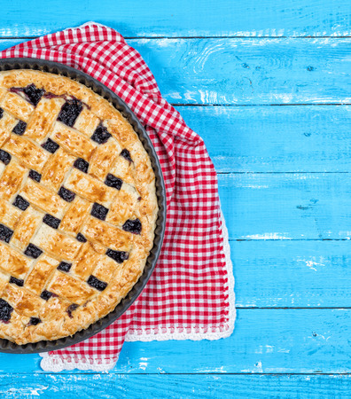 half of fruit pie on blue wooden background, copy space