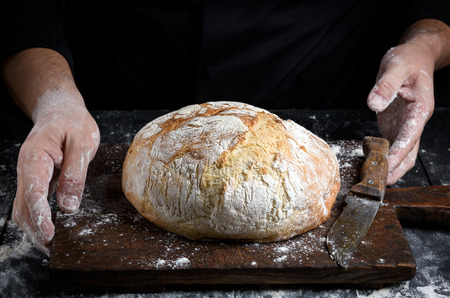 round baked homemade bread on an old brown wooden board and chef hands