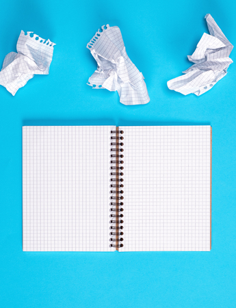 open blank notebook with white sheets on a blue background, next to two crumpled sheets Archivio Fotografico
