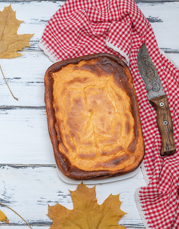 whole rectangular pie of cottage cheese and pumpkin on a white wooden table, top view