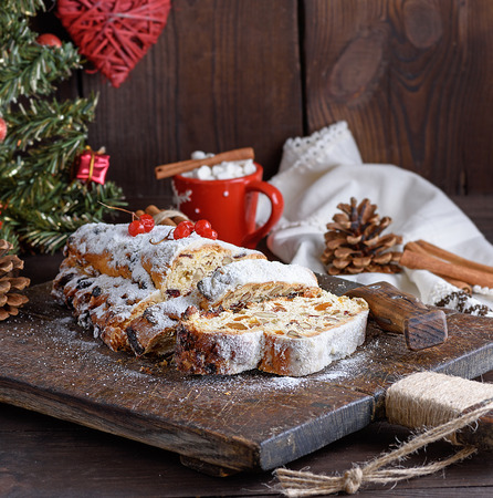 Stollen a traditional European cake with nuts and candied fruit, is dusted with icing sugar and cut into pieces on a brown wooden board