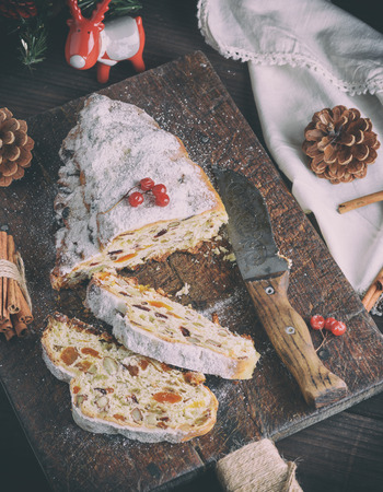 Stollen baked traditional European cake with nuts and candied fruits sprinkled with powdered sugar and cut into pieces on a brown wooden board, top view
