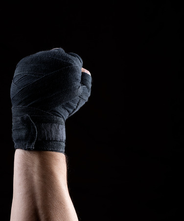 male right hand is wrapped in a black sports textile bandage on a black background, copy space Zdjęcie Seryjne