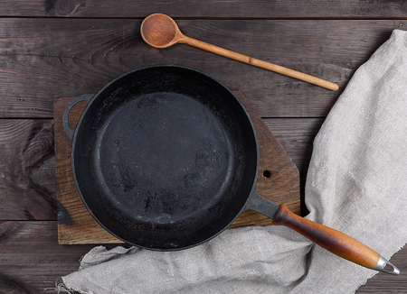 empty black round pan with wooden handle and wooden spoon on a brown table, top view