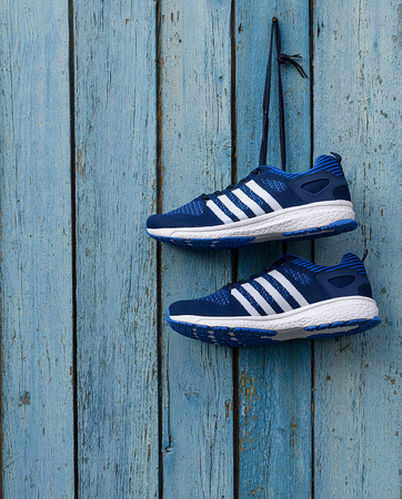 pair of male blue textile sneakers  on a blue wooden wall