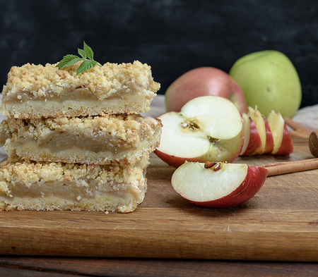 baked slices of pie with apples on a brown wooden board, close up Standard-Bild