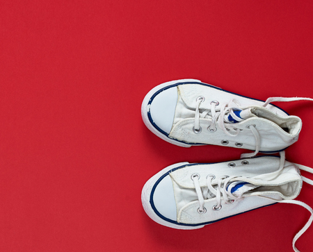 pair of white old textile sneakers with untied laces on a red background, top view
