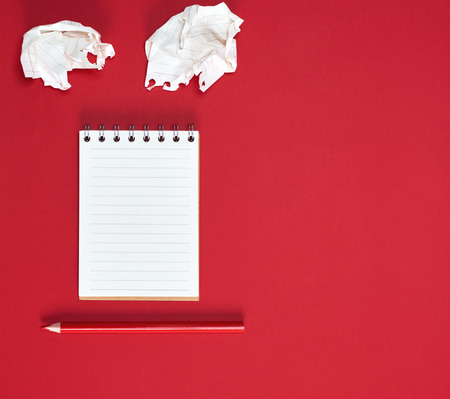 small notebook with empty white sheets in line and red wooden pencil, red background, copy space