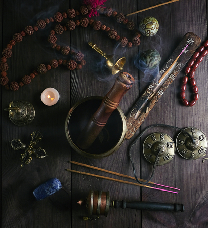 singing bowl, prayer beads, prayer drum, stone balls and other Tibetan religious objects for meditation and alternative medicine on a brown  wooden background, top view Imagens