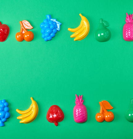 multicolored plastic toys fruits on a green background, copy space Stock Photo