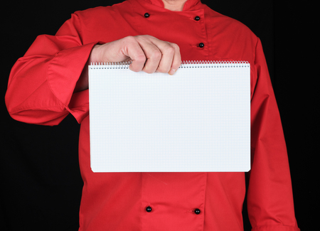 chef in red uniform holding open notepad with empty white sheets in a cell, black background
