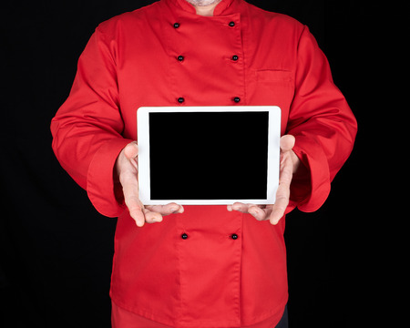 chef in a red uniform holding a white electronic tablet with a black blank screen 版權商用圖片