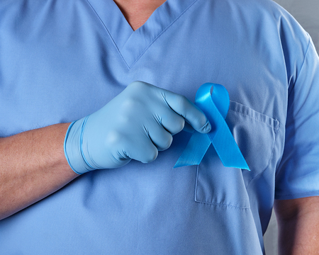 doctor in uniform and latex gloves holding a blue ribbon in his hand, a symbol of the fight and treatment of prostate cancer