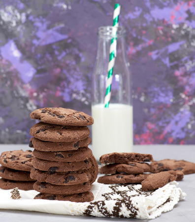 baked round chocolate chip cookies and a glass bottle with milk o